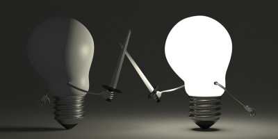 Glowing Light Bulb Fighting Against Switched Off One On Gray