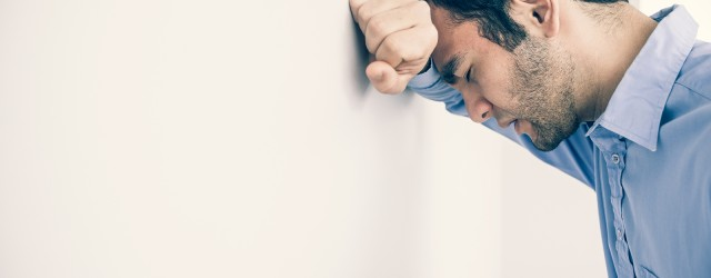Depressed man with fist clenched leaning his head against a wall