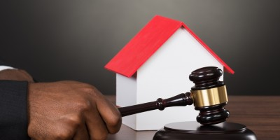 Judge Hands Hitting Gavel With House Model